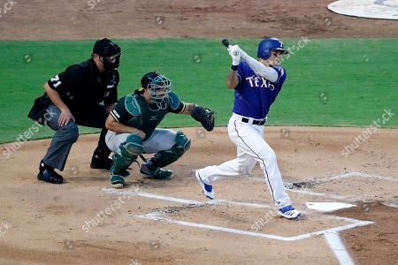 Stock Image of Shin-Soo Choo, Josh Phegley, Jordan Baker. Texas Rangers' Shin-Soo Choo, right, singles to right as Oakland Athletics catcher Josh Phegley, center, and umpire Jordan Baker look on in the first inning of a baseball game in Arlington, Texas