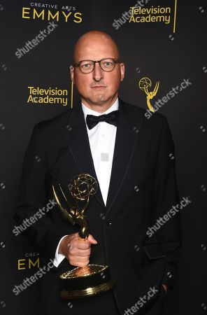 """Dan Reed poses with the award for outstanding documentary or nonfiction special for """"Leaving Neverland"""" on night one of the Television Academy's 2019 Creative Arts Emmy Awards, at the Microsoft Theater in Los Angeles"""