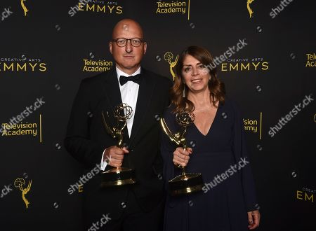 """Dan Reed, Nancy Abraham. Dan Reed, left, and Nancy Abraham, pose with the award for outstanding documentary or nonfiction special for """"Leaving Neverland"""" on night one of the Television Academy's 2019 Creative Arts Emmy Awards, at the Microsoft Theater in Los Angeles"""