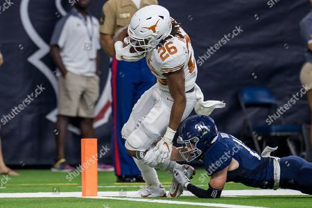 Texas Longhorns running back Keaontay Ingram (26) runs for a touchdown as Rice Owls cornerback Andrew Bird (15) attempts to bring him down during the 2nd quarter of an NCAA football game between the Texas Longhorns and the Rice Owls at NRG Stadium in Houston, TX. Texas won the game 48 to 13