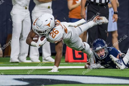 Texas Longhorns running back Keaontay Ingram (26) scores a touchdown while being tripped up by Rice Owls cornerback Andrew Bird (15) during the 2nd quarter of an NCAA football game between the Texas Longhorns and the Rice Owls at NRG Stadium in Houston, TX