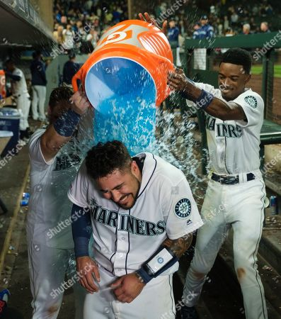 Seattle Mariners' Omar Narvaez is doused by teammates Daniel Vogelbach, left, and Dee Gordon after hitting a solo home run off of Chicago White Sox relief pitcher Alex Colome during the 10th inning of a baseball game, in Seattle. The Mariners won 2-1