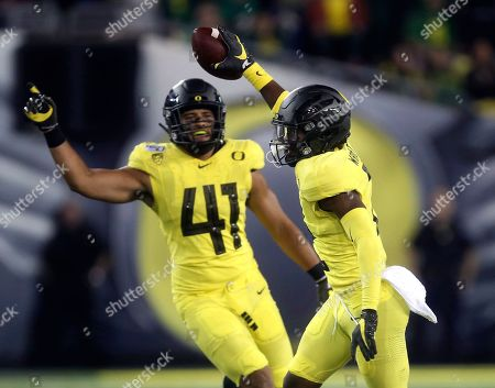 Oregon's Mykael Wright, right, celebrates a third quarter interception against Montana with teammate Isaac Slade-Matautia, left, during an NCAA college football game, in Eugene, Ore