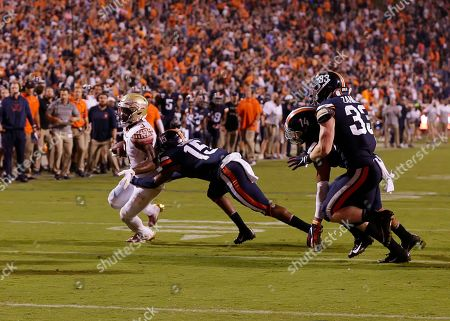 Stock Image of Florida State Seminoles RB #3 Cam Akers is dragged down by Virginia Cavaliers FS #15 De'Vante Cross to end the game during NCAA football game between the University of Virginia Cavaliers and the Florida State Seminoles at Scott Stadium in Charlottesville, Virginia
