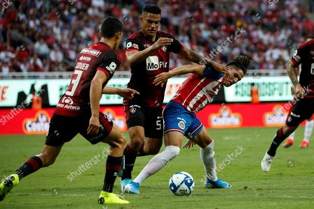 Chivas' Alan Cervantes (R) vies for the ball against Atlas' Ismael Govea (L) and Anderson Santamaria (C) during a match between Atlas and Chivas of the Mexican Tournament held at the Akron stadium in Guadalajara, Mexico, 14 September 2019. EFE/ Francisco Guasco