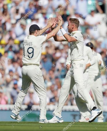 England's Stuart Broad, right, and England's Chris Woakes celebrate the wicket of Australia's Marcus Harris during the fourth day of the fifth Ashes test match between England and Australia at the Oval cricket ground in London
