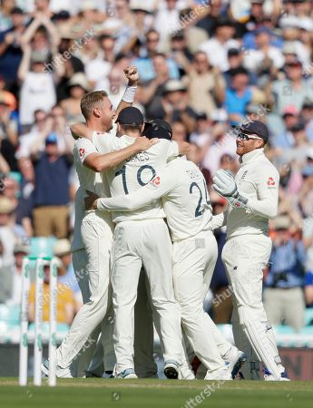 England's Stuart Broad, left, celebrates taking the wicket of Australia's David Warner during the fourth day of the fifth Ashes test match between England and Australia at the Oval cricket ground in London
