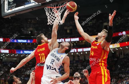 Victor Claver (L) and Willy Hernangomez Geuer (R) of Spain in action against Marcos Delia of Argentina during the FIBA Basketball World Cup 2019 final match between Argentina and Spain, in Beijing, China, 15 September 2019.
