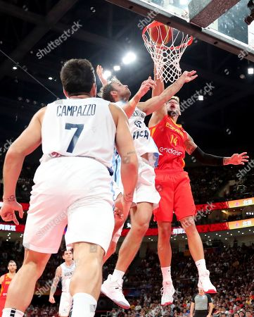 Spain's Willy Hernangomez Geuer tries to dunk near Argentina's Marcos Delia, center and Argentina's Facundo Campazzo at left during the final of the FIBA Basketball World Cup held at the Cadillac Arena in Beijing, Sunday, Sept. 15, 2019.