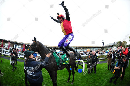 CURRAGH. Pat Smullen Champions Race. TONY McCOY doing a flying dismount from QUIZICAL after his win.