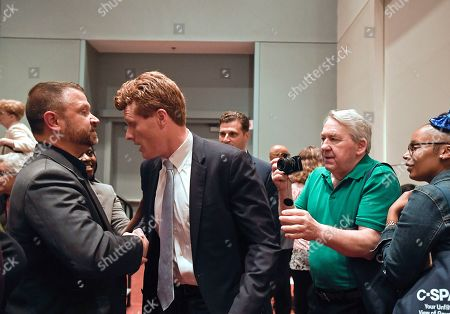 U.S. Rep. Joe Kennedy III, is stopped by people who want to meet him as he leaves a panel on race and politics, in Springfield, Mass