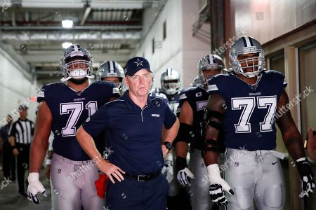 Week 2. Dallas Cowboys head coach Jason Garrett, center, and members of the team prepare to take the field before the start of an NFL football game against the Washington Redskins, in Landover, Md. With Garrett are Dallas Cowboys offensive tackle La'el Collins (71) and offensive tackle Tyron Smith (77