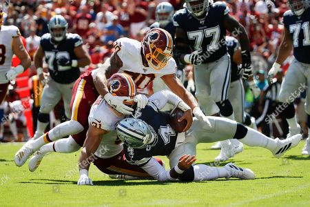 Week 2. Dallas Cowboys quarterback Dak Prescott (4) is sacked by Washington Redskins linebackers Ryan Kerrigan (91) and Montez Sweat (90) in the first half of an NFL football game, in Landover, Md