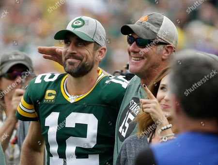 Green Bay Packers' Aaron Rodgers smiles with former quarterback Brett Favre during halftime of an NFL football game against the Minnesota Vikings, in Green Bay, Wis