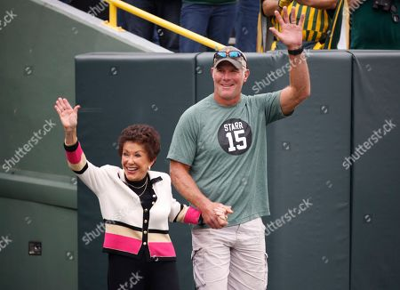 Stock Picture of Former Green Bay Packers quarterback Brett Favre escorts Sherry Starr out of the tunnel before an NFL football game between the Green Bay Packers and the Minnesota Vikings, in Green Bay, Wis