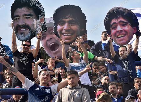 Fans of Diego Maradona hold up cut-outs of his face during a local tournament soccer match between Maradona's new team as coach of Gimnasia y Esgrima La Plata, and Racing Club at Juan Carmelo Zerillo stadium in La Plata, Argentina