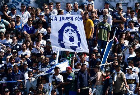 Fans hold up a banner of Diego Maradona, head coach of Gimnasia y Esgrima La Plata soccer team, prior to a local tournament soccer match against Racing Club at Juan Carmelo Zerillo stadium in La Plata, Argentina