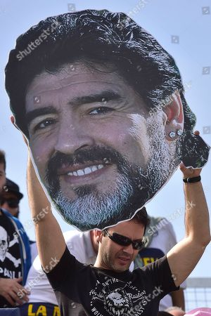 A fan of the Gimnasia y Esgrima La Plata soccer team holds up a photo of the new head coach, Diego Maradona, at a local tournament soccer match against Racing Club at Juan Carmelo Zerillo stadium in La Plata, Argentina