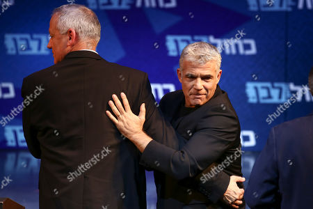 Blue and White party leaders, Benny Gantz, left, and Yair Lapid go up on stage during an election campaign in Tel Aviv, Israel, . Israel will hold general elections on Sept. 17