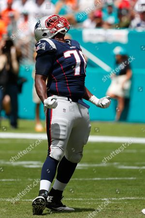 New England Patriots defensive tackle Adam Butler (70) celebrates after sacking Miami Dolphins quarterback Ryan Fitzpatrick (14), during the first half at an NFL football game, in Miami Gardens, Fla