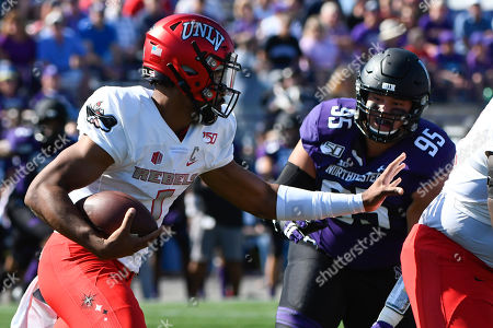 Stock Image of Armani Rogers, Alex Miller. UNLV quarterback Armani Rogers (1) runs against Northwestern defensive lineman Alex Miller (95) during the first half of an NCAA college football game on . in Evanston, Ill