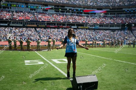 Taj George, wife of former Tennessee Titans running back Eddie George, sings the national anthem before an NFL football game between the Titans and the Indianapolis Colts, in Nashville, Tenn. Eddie George's number is to be retired at halftime. Taj George is a member of the R&B singing group Sisters with Voices