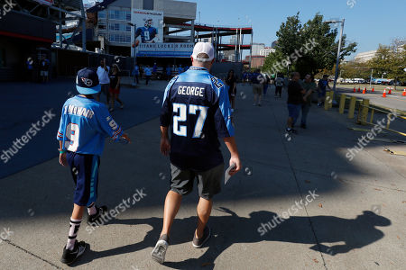 Tennessee Titans fans wearing the jersey numbers of the late Tennessee Titans quarterback Steve McNair and former running back Eddie George arrive at Nissan Stadium before an NFL football game between the Tennessee Titans and the Indianapolis Colts, in Nashville, Tenn. The numbers of McNair and George were retired by the team during halftime