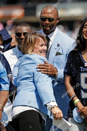 Tennessee Titans owner Amy Adams Strunk hugs former running back Eddie George during a ceremony retiring George's number during an NFL football game between the Titans and the Indianapolis Colts, in Nashville, Tenn