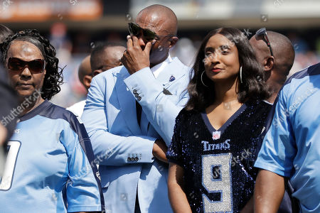 Former Tennessee Titans running back Eddie George, center, wipes his eyes as his number 27 is retired during a halftime ceremony at an NFL football game between the Titans and the Indianapolis Colts, in Nashville, Tenn. The number 9 of the late Titans quarterback Steve McNair was also retired