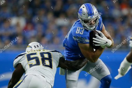Detroit Lions tight end Jesse James (83) lies to avoid Los Angeles Chargers outside linebacker Thomas Davis (58) after making a catch in the first half of an NFL football game in Detroit