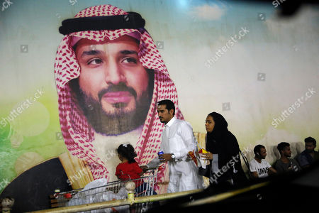 A Saudi family walk past a giant poster of Saudi Crown Prince Mohammed bin Salman, at a shopping mall in Jiddah, Saudi Arabia, . The weekend drone attack on one of the world's largest crude oil processing plants that dramatically cut into global oil supplies is the most visible sign yet of how Aramco's stability and security is directly linked to that of its owner -- the Saudi government and its ruling family