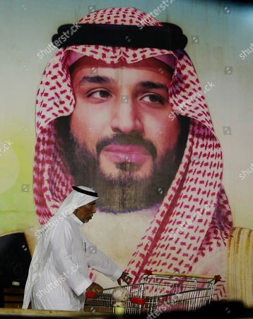 A man walks under a giant poster showing Saudi Crown Prince Mohammed bin Salman Jiddah, Saudi Arabia, . The weekend drone attack on one of the world's largest crude oil processing plants that dramatically cut into global oil supplies is the most visible sign yet of how Aramco's stability and security is directly linked to that of its owner _ the Saudi government and its ruling family