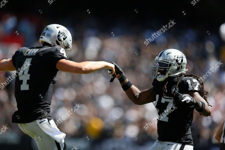 Oakland Raiders quarterback Derek Carr is greeted by wide receiver Dwayne Harris (17) during the first half of an NFL football game against the Kansas City Chiefs, in Oakland, Calif