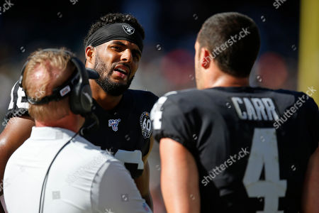 Oakland Raiders wide receiver Tyrell Williams talks on the sidelines with quarterback Derek Carr and head coach Jon Gruden, left, during the second half of an NFL football game, in Oakland, Calif. Kansas City won the game 28-10