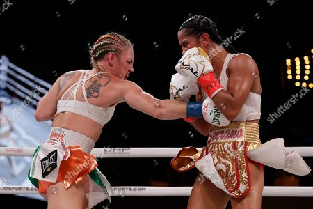 Heather Hardy, left, punches Amanda Serrano during the ninth round of a WBO world female featherweight championship boxing match, in New York. Serrano won the fight
