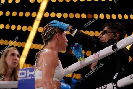 A doctor checks on Heather Hardy before the start of the second round of a WBO world female featherweight championship boxing match against Amanda Serrano, in New York. Serrano won the fight