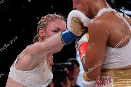Heather Hardy, left, punches Amanda Serrano during the eighth round of a WBO world female featherweight championship boxing match, in New York. Serrano won the fight