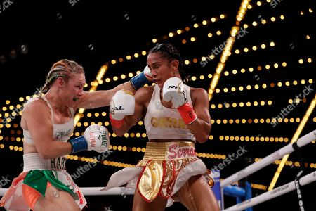 Heather Hardy, left, punches Amanda Serrano during the fourth round of a WBO world female featherweight championship boxing match, in New York. Serrano won the fight