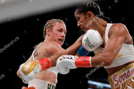 Heather Hardy, left, punches Amanda Serrano during the third round of a WBO world female featherweight championship boxing match, in New York. Serrano won the fight