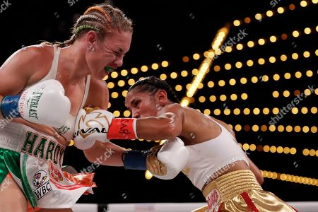 Amanda Serrano, right, punches Heather Hardy during the fifth round of a WBO world female featherweight championship boxing match, in New York. Serrano won the fight