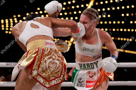 Amanda Serrano, left, punches Heather Hardy during the eighth round of a WBO world female featherweight championship boxing match, in New York. Serrano won the fight