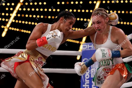 Amanda Serrano, left, fights Heather Hardy during the second round of a WBO world female featherweight championship boxing match, in New York. Serrano won the fight