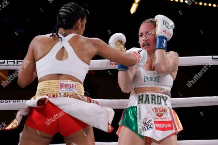Amanda Serrano, left, punches Heather Hardy during the first round of a WBO world female featherweight championship boxing match, in New York. Serrano won the fight