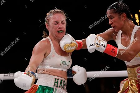 Amanda Serrano, right, punches Heather Hardy during the fourth round of a WBO world female featherweight championship boxing match, in New York. Serrano won the fight