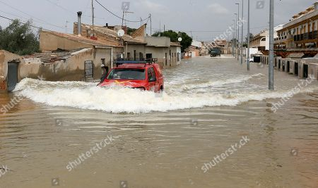 A man drives his car through a flooded street of La Daya Vieja, Alicante, eastern Spain, 15 September 2019. A total of six people have died due to the 'gota fria' (cold drop) phenomenon in the Mediterranean coast of Spain.