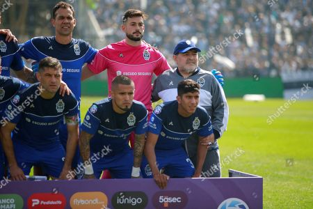 Gimnasia y Esgrima head coach, Argentina Diego Maradona (R), poses with his players during a game against Racing Club, at the Juan Carmelo Zerillo Stadium, in La Plata, Argentina, 15 September 2019.