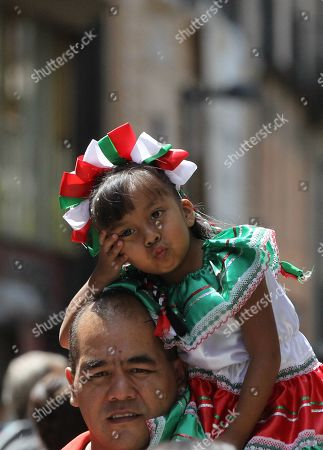 A man carries a girl in typical clothing as they approach the vicinity of the Zocalo square, in Mexico City, Mexico, 15 September 2019. With musical festivals and typical food stalls, thousands of Mexicans began to fill the country's squares to commemorate the Independence Festivities that will have their peak on Sunday night with the Grito ceremony headed by the president of Mexico, Andres Manuel Lopez Obrador, in the National Palace.