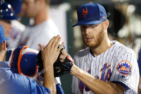 Teammates greet New York Mets starting pitcher Zack Wheeler in the dugout after the sixth inning of a baseball game against the Los Angeles Dodgers, in New York. Wheeler pitched seven innings in the game, allowing one run on six hits