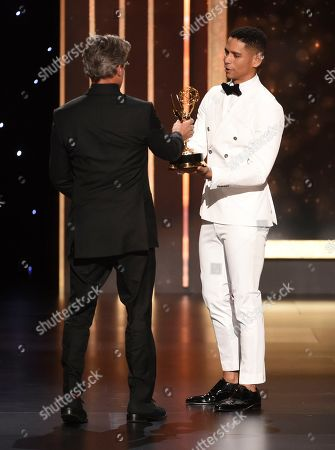 "Angus Wall, left, accepts the award from Charlie Barnett for outstanding main title design for ""Game of Thrones"" on night two of the Television Academy's 2019 Creative Arts Emmy Awards, at the Microsoft Theater in Los Angeles"