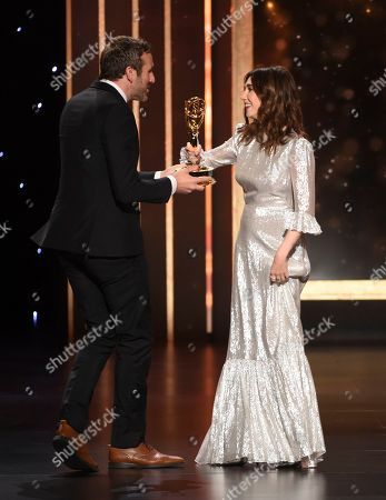"""Chris O'Dowd, Carice Van Houten. Carice Van Houten, right, presents the award to Chris O'Dowd, winner of the award for outstanding short form comedy or drama for """"State of the Union"""" on night two of the Television Academy's 2019 Creative Arts Emmy Awards, at the Microsoft Theater in Los Angeles"""